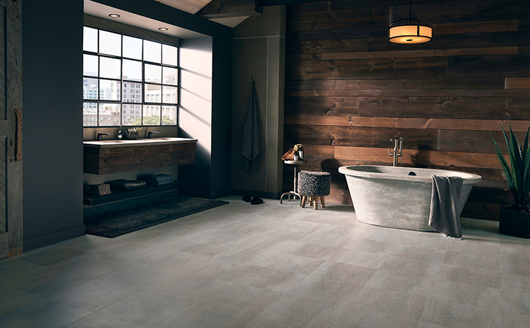 Open concept bathroom with light tile floor, wood plank wall, and free standing tub and sink